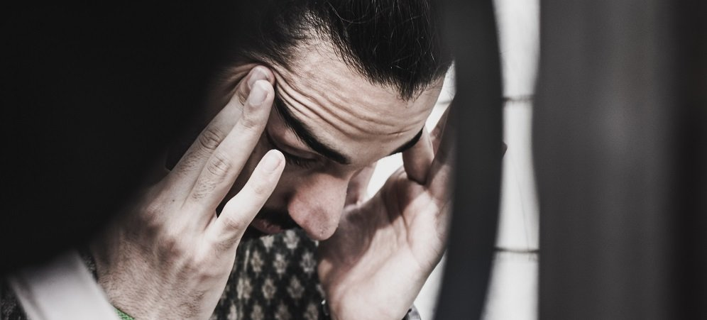 Man rubbing his temples looking stressed