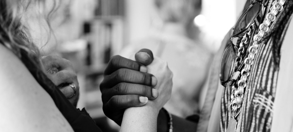 Man and woman grasping hands to make peace