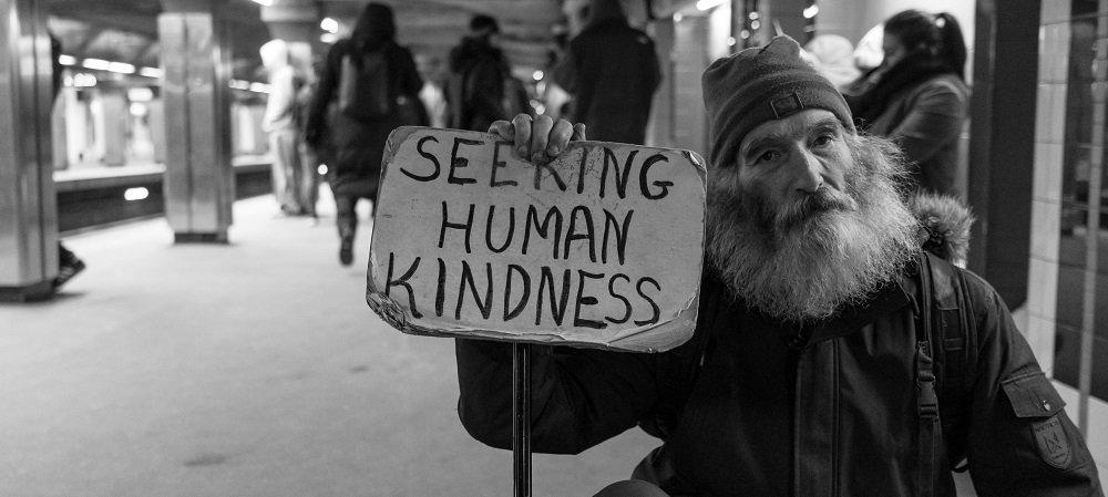 Older man holding sign that reads Seeking Human Kindness