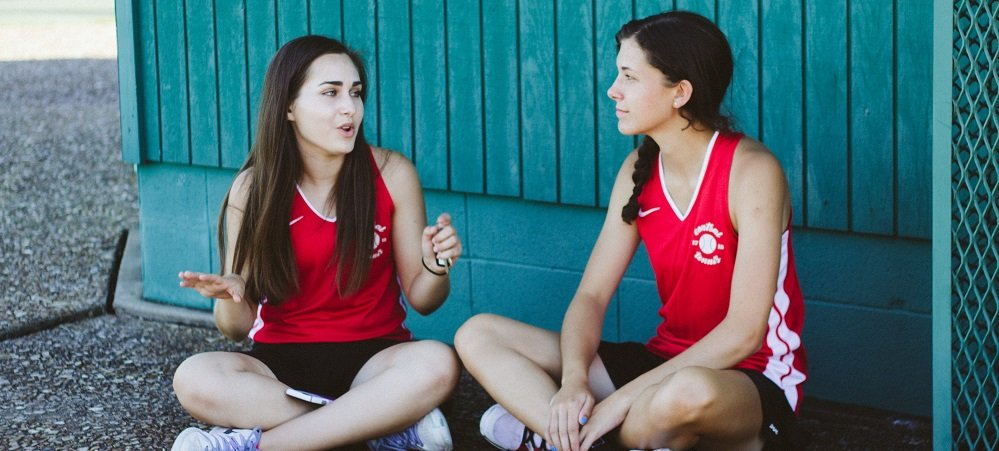 Two teen athletes talking to each other