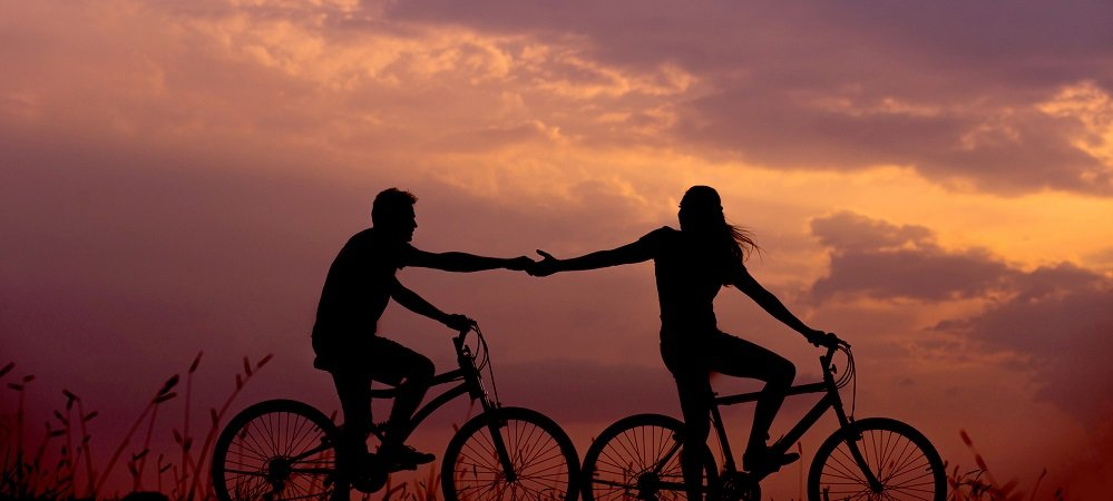 Silhouette of man and woman riding bicycles