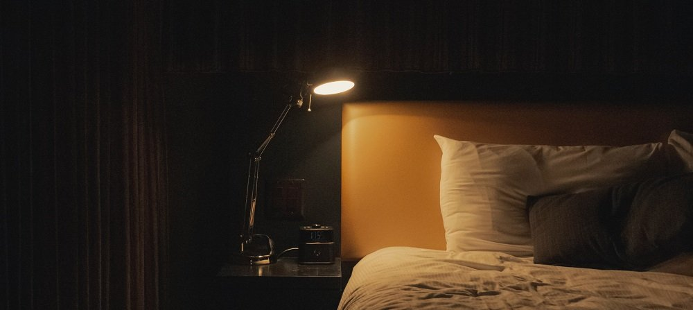 Lamp on table by bed in dark room