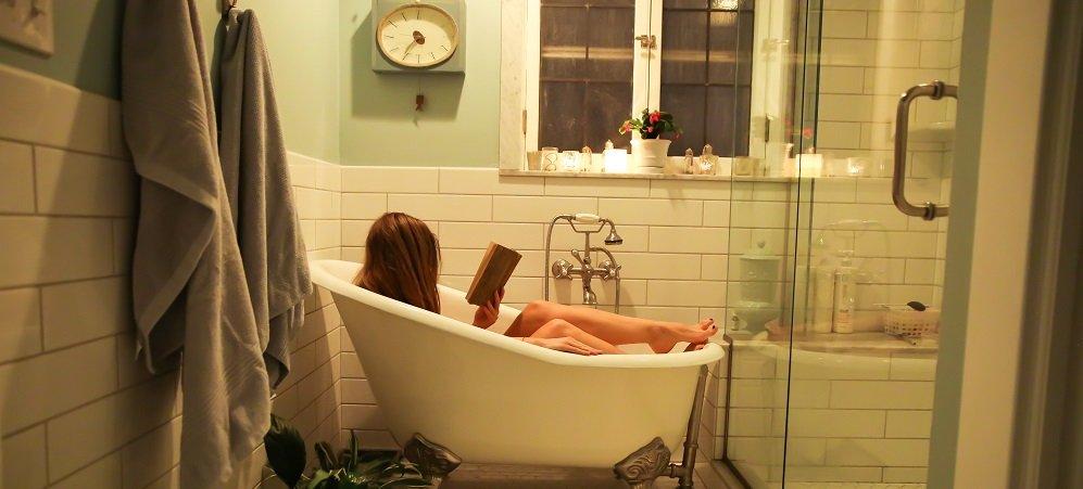 Girl reading book in bathtub