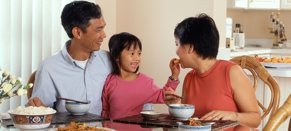 Smiling parents and child at dinner table